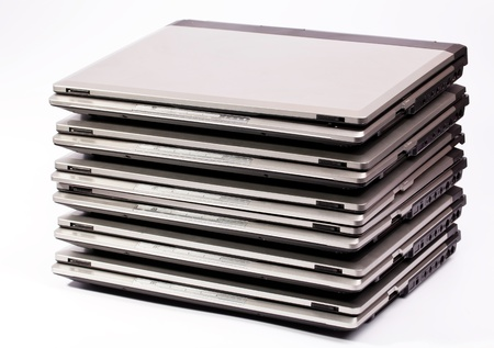 Pile of laptops on the white background Stock Photo