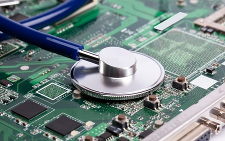 Laptop green motherboard with stetoscope on it Stock Photo