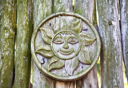 Pagan wooden sun sign on a log