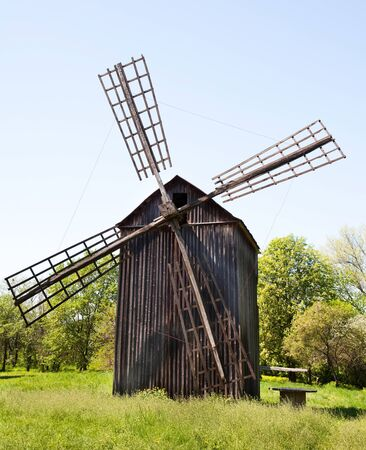Wooden windmill near forest