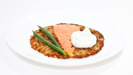 Rosti with salmon and sour cream on the white plate