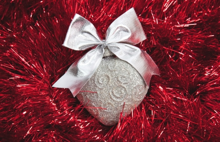 Silver Christmas heart on red tinsel background photo
