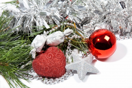 Red Christmas balls and silver star with candy on pine branch Stock Photo