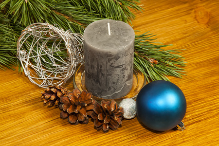New Year 2017 composition with fir cones and grey candle on wooden background
