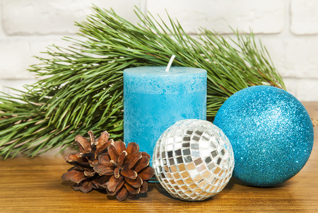 New Year 2017 composition with bright blue glitter ball and candle on wooden back ground