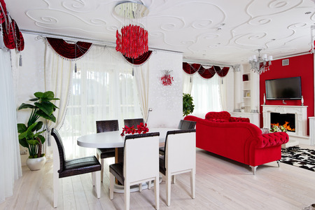 Classical living room interior in white and red colors with dinner table and fireplace