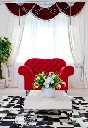 Red classical armchair in bright living room interior Stock Photo
