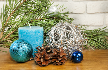 New Year 2017 composition with bright blue ball and candle on wooden background woth fir tree branch