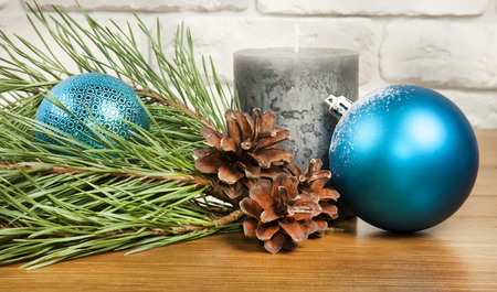 New Year and Christmas composition with fir cones and  candle on wooden and brick background Stock Photo