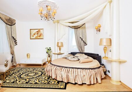 Golden classical bedroom interior with round bed and small table. Bedroom interior design.