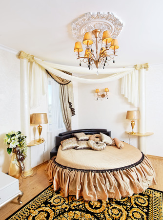 Golden classical bedroom interior with round bed and ornate ceiling
