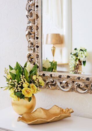 Golden vintage vase with flowers near beautiful antique mirror Stock Photo