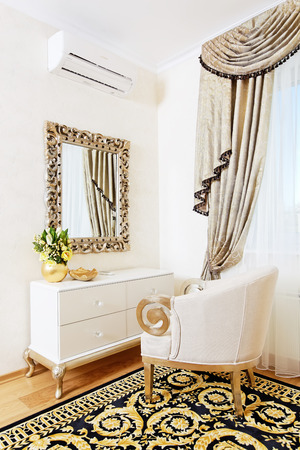 White console-mirror with chair in golden bedroom design Stock Photo