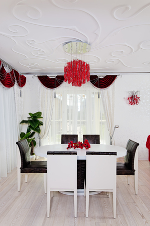 White glossy table with chairs in white and red classical interior