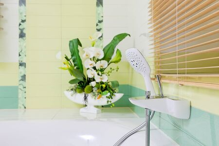 Beautiful white faucet on bathtube  with flowers decor
