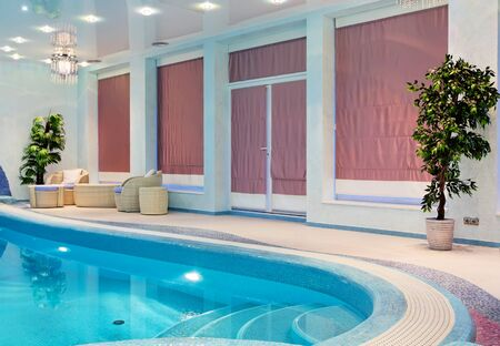 Relaxation zone near blue mosaic swimming pool with furniture