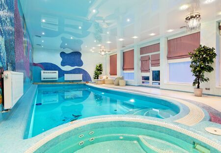 Swimming pool interior design with blue mosaic and plants