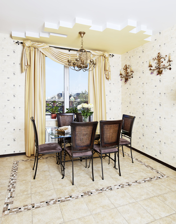 Dining table and chair in yellow kitchen with golden lamp