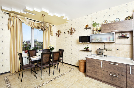 Beautiful wooden kitchen with dinner table and chairs Stock Photo