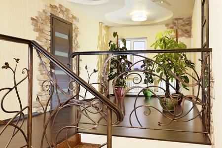 Classical stairs with ornamental handrail in hallway with doors and stone decors Stock Photo