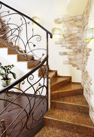 Classical mosaic stairs with ornamental handrail in hallway with stone decors