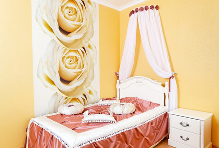 Beautiful bedroom yellow interior with roses and fabric pillows Stock Photo