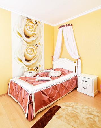Beautiful classical bedroom interior in yellow colors with fabric pillows Stock Photo