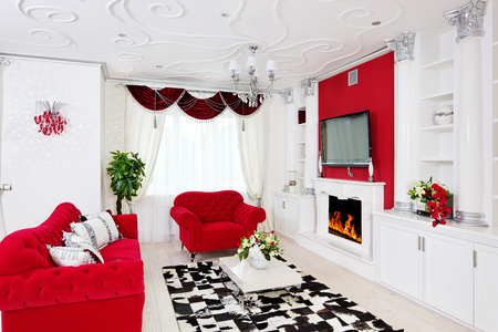 Classical living room interior in white and red with fireplace and columns