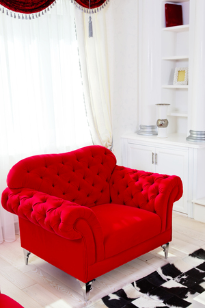 Red classical armchair and white curtains in interior