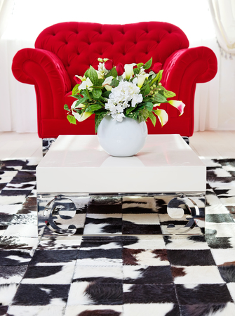 Red classical armchair in living interior with flowers on coffee table