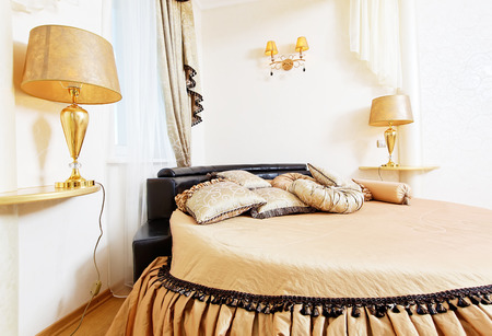 Cozy soft beautiful round bed in classical golden bedroom close up