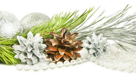 Fir tree branch and cones with silver ball isolated on white backround