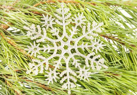 Artificial new year snowflake on fir tree branch background close up