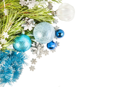 Fir tree branch and cones with blue balls and tinsel isolated on white