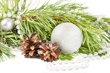 New year composition with fir tree, cones and silver ball on white background