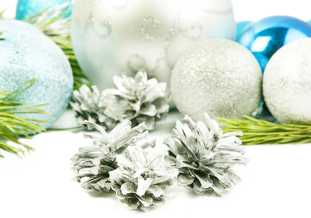 New year composition with fir tree branch, beautiful silver ball and silver cones close up Stock Photo