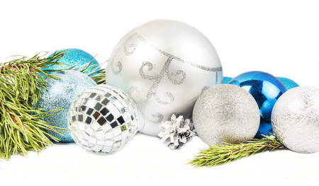 New year and Christmas composition with fir tree branch, beautiful silver ball and blue balls  on white background