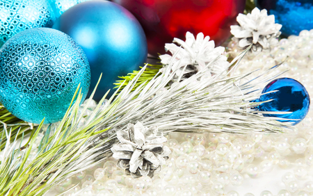 New year decorations on white beads background with balls and fir tree branch