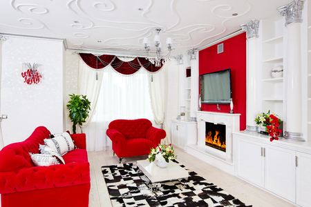 Classical red living room interior with fire place, red furniture and beautiful flowers
