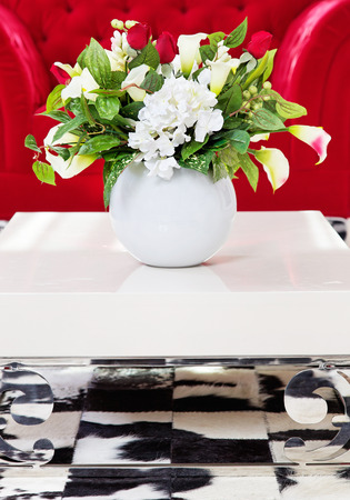Artificial flowers in white vase in living room interior on white glossy coffee table Stock Photo