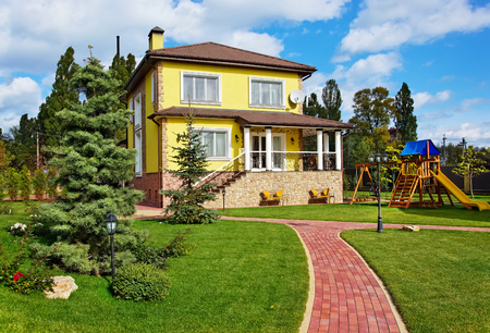Exterior of luxury home with green yard, trees and children playground
