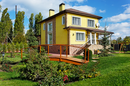Exterior of luxury home with green yard and wooden bridge in landscape design Фото со стока