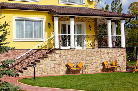 Exterior of luxury home with terrace, green yard and beautiful iron benches