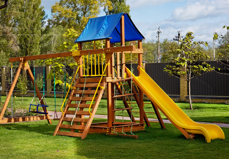 Outdoor children wooden playground in sunny day Фото со стока