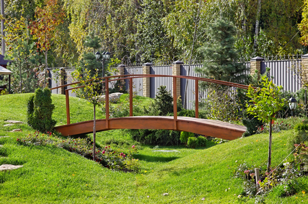 Wooden bridge in a beautiful garden with green grass and evergreen trees Фото со стока