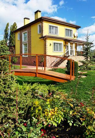 Beautiful yellow house in garden with bridge Фото со стока