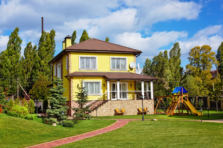 Exterior of beautiful house with green loan and children playground