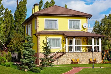 Exterior of beautiful house with green yard and children playground Фото со стока