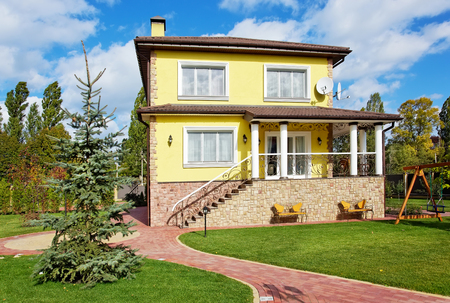 Exterior of luxury house with green grass loan and children playground Фото со стока