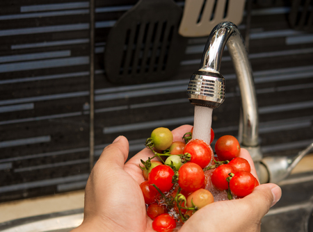 Hands cleaning tomatoes under the wate Tap,Healthy concept.focus on tap photo